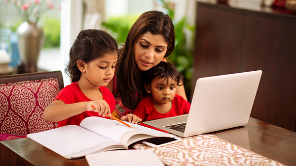a mother sitting at her computer with her two children